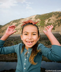 An adorable young pree teen girl with missing teeth in front and a starfish balanced on her head. The little girl is having fun at the beach playing with creatures from the sea. She is wearing a long sleeved blue sweater.